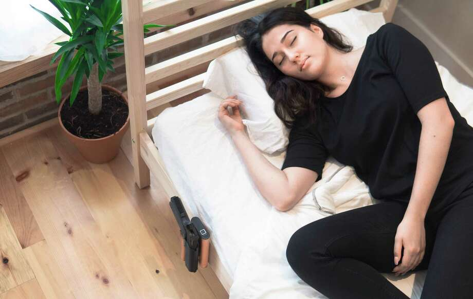 Vara Safety of Latham produces the Reach biometric holster, pictured in this photo staged by the company to show how it can be easily attached to a bed or bed stand. Photo: Vara Safety