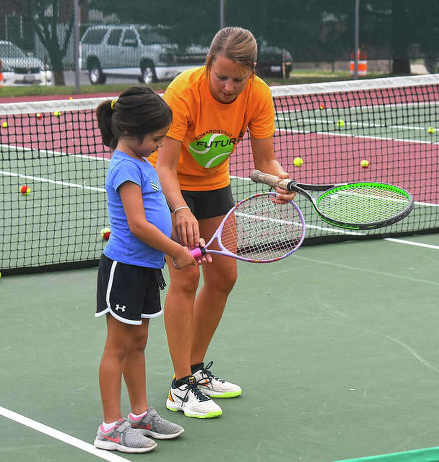 Emily Cimarolli, right, shows how to hold a racket to hit a shot during the Edwardsville Futures Kids' Night on Aug. 5 at the EHS Tennis Center. Photo: Intelligencer File Photos