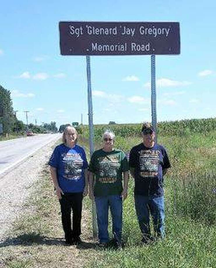 Joan Page, Kathy Robinson and Richard Gregory, from left, stand in front of a sign denoting the Sgt. Glenard Gregory Memorial Highway outside of Shipman.