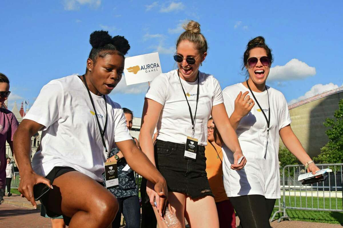 From left, artistic gymnast Alicia Boren of New Jersey, basketball player Rebecca Cole of Australia and basketball player Kalani Purcell of New Zealand have fun as they march with other athletes as part of the official Aurora Games kickoff ceremony at the Empire State Plaza on Monday, Aug. 19, 2019 in Albany, N.Y. (Lori Van Buren/Times Union)