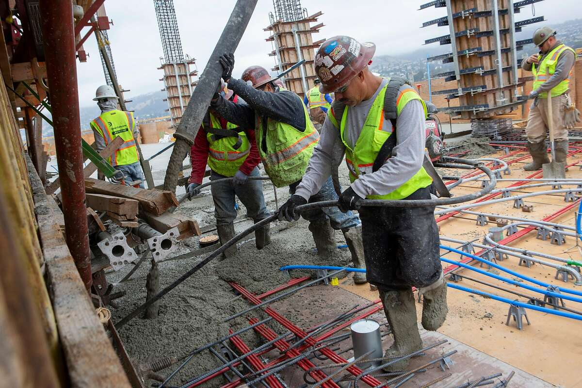 Construction workers pour a deck on the 24th floor of the MacArthur Commons construction site on Monday, July 8, 2019, in Oakland, Calif.