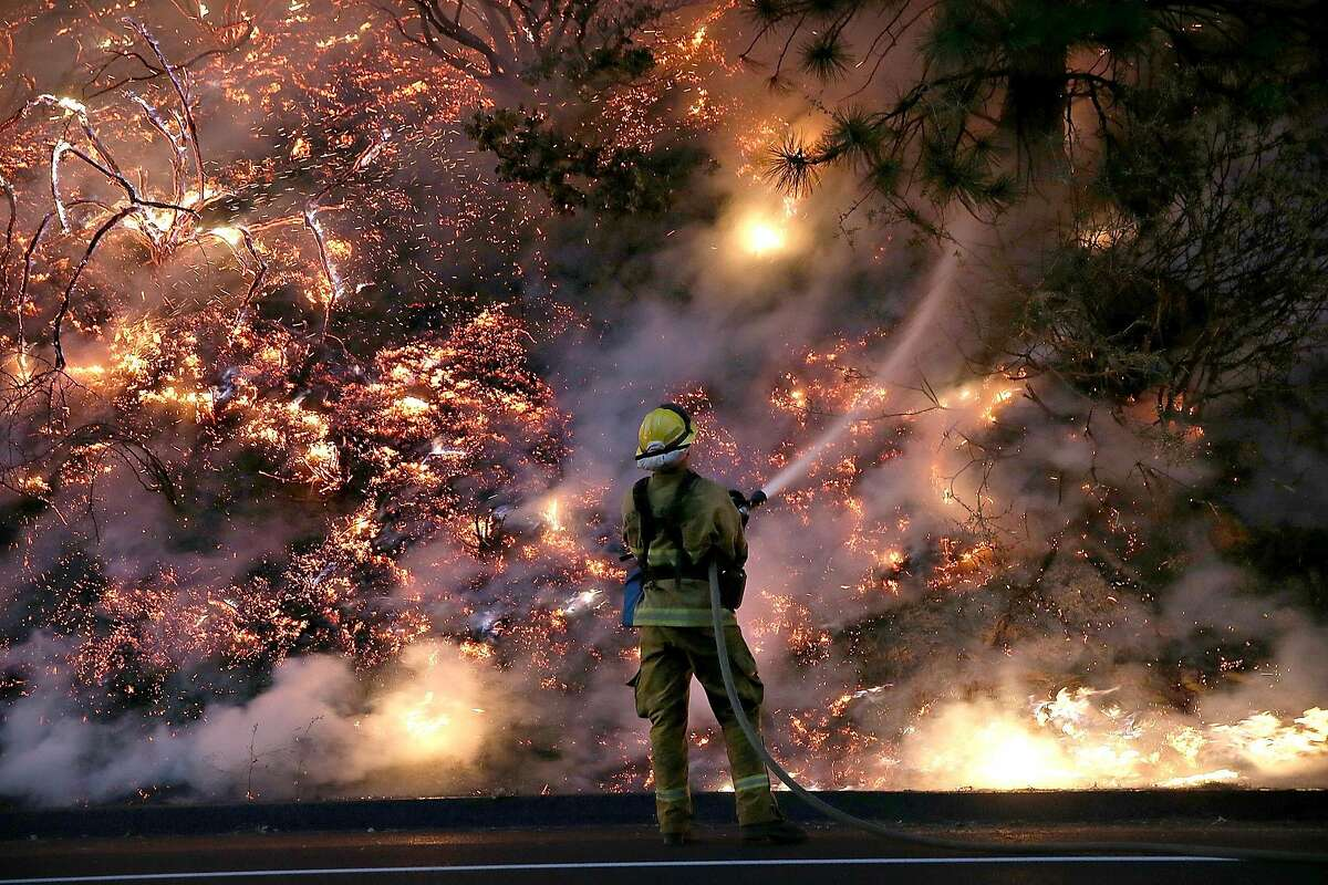 GROVELAND, CA - AUGUST 24: A firefighter uses a hose to douse the flames of the Rim Fire on August 24, 2013 near Groveland, California. The Rim Fire continues to burn out of control and threatens 4,500 homes outside of Yosemite National Park. Over 2,000 firefighters are battling the blaze that has entered a section of Yosemite National Park and is currently 5 percent contained. (Photo by Justin Sullivan/Getty Images) ***BESTPIX***