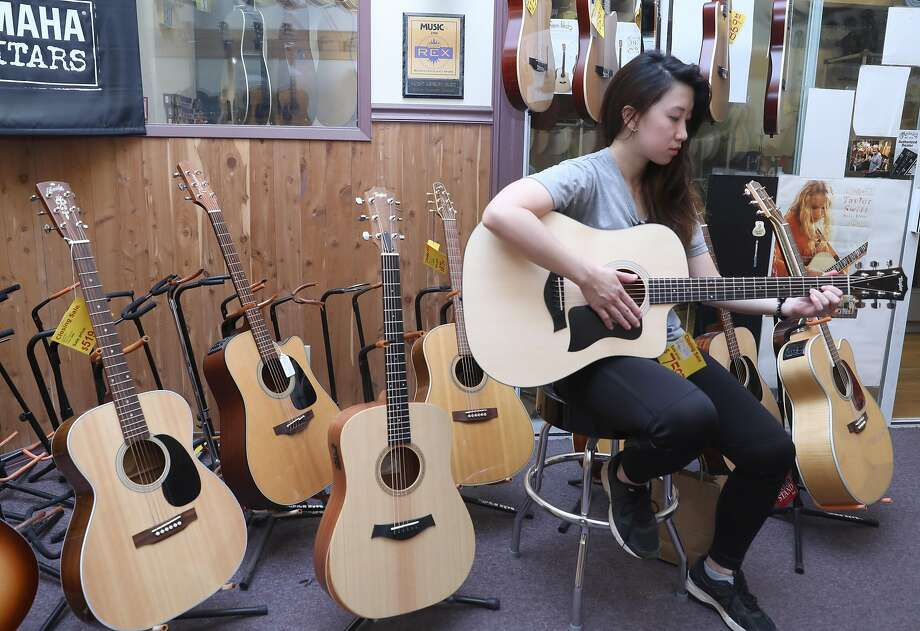 Twinkle Tay from Singapore checks out an acoustic guitar at the Haight Ashbury Music Center. The independent shop is closing after almost five decades in the face of higher rent and online competition. Photo: Liz Hafalia / The Chronicle