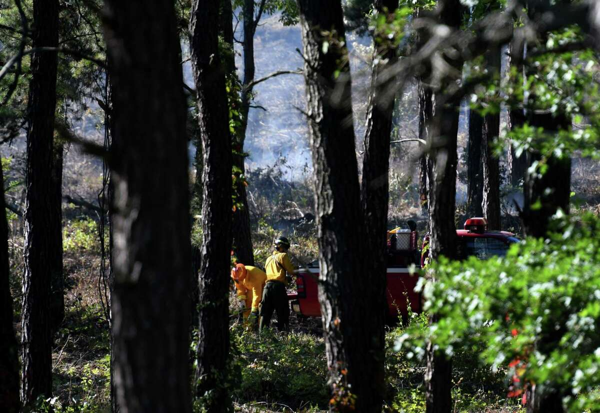 Crews put out hot spots following a controlled burn in the Albany Pine Bush Preserve between Route 155 and I-90 on Friday, Sept.13, 2019, in Albany, N.Y. (Will Waldron/Times Union)