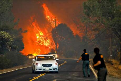 Thursday, Nov. 8, 2018: Butte County sheriff's deputies try to direct panicked drivers fleeing the onrushing Camp Fire along Pentz Road in Paradise, Calif.  With few escape routes out of the small rural community, many drivers would become stuck in traffic jams and have to abandon their vehicles to the fire.  Photo: Gabrielle Lurie