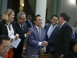 Assemblyman David Chiu,D-San Francisco, center, is congratulated by Assemblyman Timothy Grayson, D-Concord, right, after his measure to cap rent increases was approved by the Assembly in Sacramento, Calif., on Wednesday, Sept. 11, 2019. The bill now goes to Gov. Gavin Newsom. Joining in the celebration are Democratic Assembly members Buffy Wicks, of Oakland, left, Richard Bloom, of Santa Monica, second from left, and Miguel Santiago, of Los Angeles, fourth from left. (AP Photo/Rich Pedroncelli)