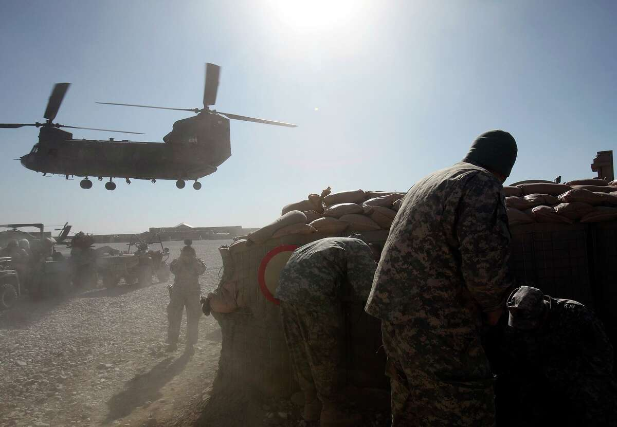 Members of Texas Army National Guard's Agribusiness Development Team 2 cover up from flying dirt as a CH-47 Chinook helicopter lands at Forward Operating Base Ghazni in this 2009 file photo.