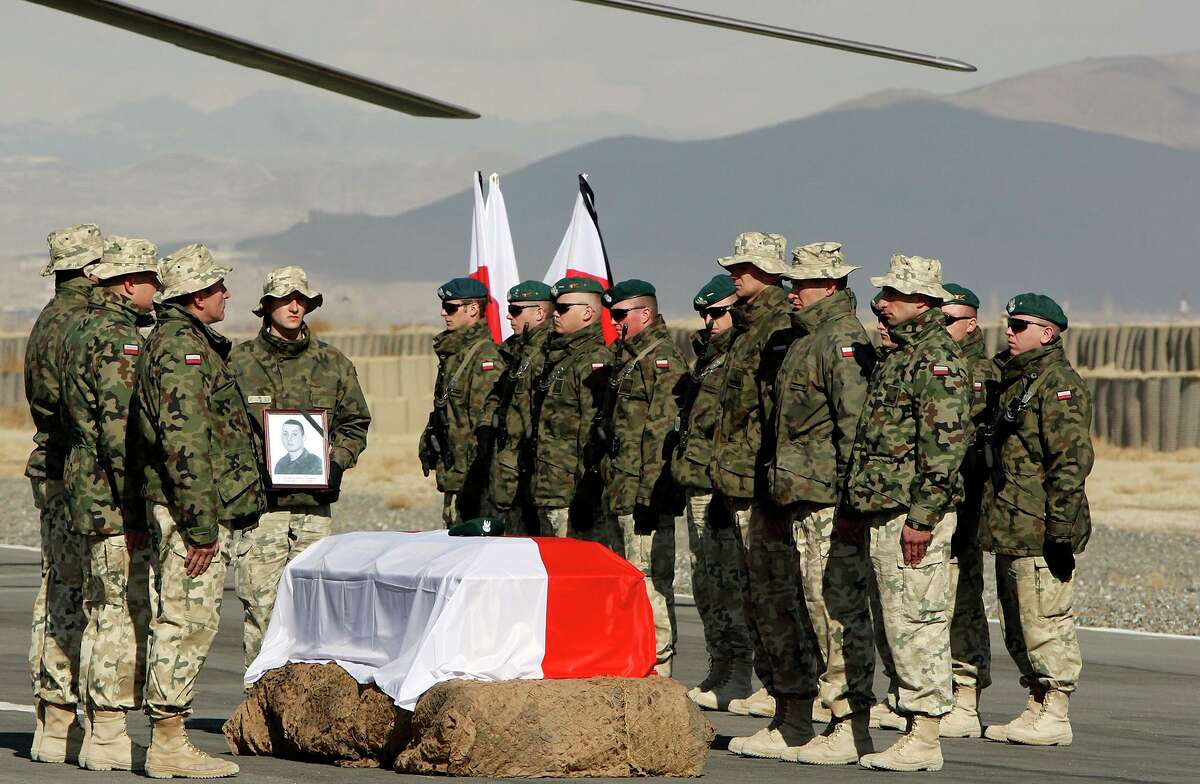 A Polish soldier holds a photo of Polish Army Pvt. 1 Michal Kolek, 22, near Kolek's flag draped casket at Forward Operating Base Ghazni before it was loaded on a helicopter for the trip home in this 2009 file photo.