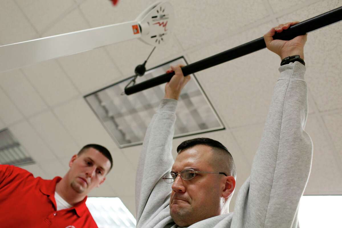 Sgt. Todd Plybon works out with physical therapy assistant Mike Barker, left, at Brooke Army Medical Center in this 2012 file photo.