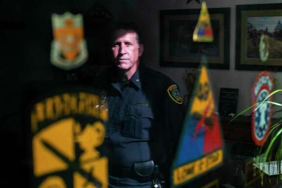 Dan Harris' reflection is seen against a glass of a frame holding military badges in his office on Thursday, Sept. 12, 2019, in Houston. Harris, a Houston Police Department commander and retired Texas Army National Guard colonel, led a team of agriculture experts in Afghanistan in 2009.