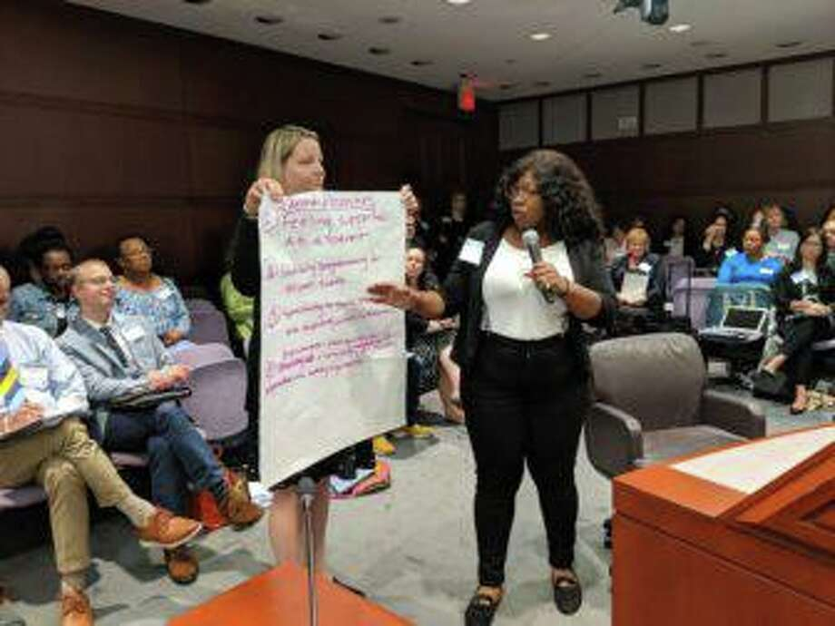 Fatima Horton, a parent from Middletown, presents a list of child care priorities reached by parents at Thursday's event. Valerie Hosley, a Yale professor who had trouble finding child care for her daughter holds the list. Photo: Kathleen Megan / CTMirror.org