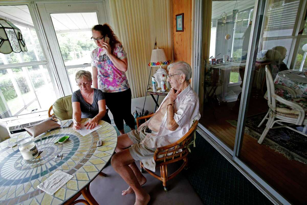 Amalie Hennech, left, and her daughter Alexis Garlini, work on evacuating their elderly friend Jack, who has advanced medical issues, during a mandatory evacuation in preparation for Hurricane Dorian, in Vero Beach, Fla.