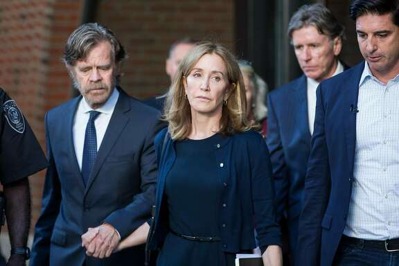 The actress Felicity Huffman leaves federal court beside her husband, the actor William Macy, after her sentencing in Boston, on Friday, Sept. 13, 2019. Huffman was sentenced to 14 days in prison for paying a college consultant $15,000 to inflate her daughter's SAT score, becoming the first parent given a punishment in a sweeping scheme in which nearly three dozen wealthy parents are accused of using lies and bribes to smooth their children's way into prestigious colleges. (Scott Eisen/The New York Times)