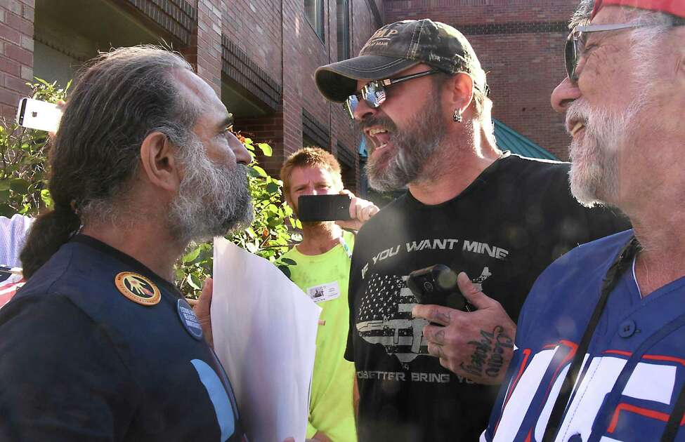 Protestor Joe Seeman of Saratoga Progressive Action, left, is confronted by President Donald Trump supporter Brook Boice of Glens Falls area, center, outside of Elise Stefanik's office on Friday, Sept. 13, 2019 in Glens Fall, N.Y. The protestors were marching in a Stefanik: Defund Hate! March & Rally. Supporters of President Donald Trump confronted the marchers. (Lori Van Buren/Times Union)