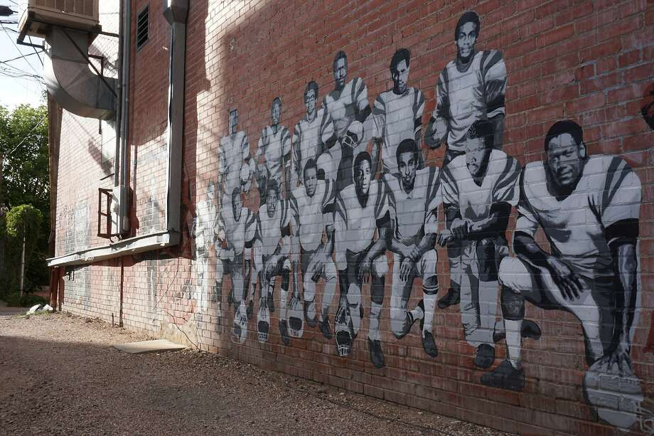 In this Wednesday, Sept. 11, 2019 photo shows part of an alleyway mural in downtown Laramie, Wyo., that honors the Black 14. The Black 14 were black athletes dismissed from the University of Wyoming football team in 1969 for seeking to protest racism by wearing black armbands in a game against Brigham Young University. The university plans to dedicate a plaque honoring the group at War Memorial Stadium on Friday. (AP Photo/Mead Gruver) Photo: Mead Gruver / Associated Press
