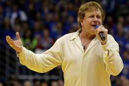 FILE - In this Jan. 25, 2010 file photo, Eddie Money sings the national anthem before an NCAA college basketball game between Kansas and Missouri in Lawrence, Kan. Family members have said Eddie Money has died on Friday, Sept. 13, 2019. (AP Photo/Charlie Riedel, File)