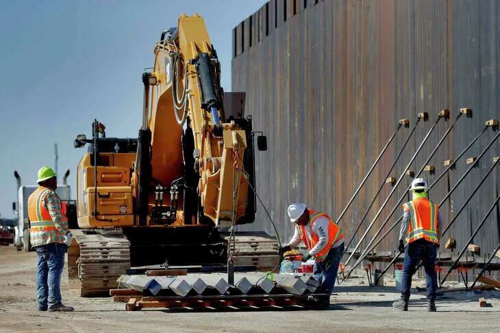Government contractors erect a section of Pentagon-funded border wall. The 30-foot high wall replaces a five-mile section of Normandy barrier and post-n-beam fencing, shown at left, along the the International border that separates Mexico and the United States. Construction began as federal officials revealed a list of Defense Department projects to be cut to pay for President Donald Trump's wall.