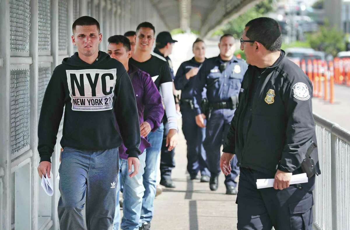 U.S. Immigration and Customs Enforcement officials return six Cuban men and one from Honduras to Mexican Immigration officials in the middle of the Gateway to the Americas International Bridge between Laredo and Nuevo Laredo on Friday, Sept. 13, 2019. The men, seeking asylum were given another court date in two months.