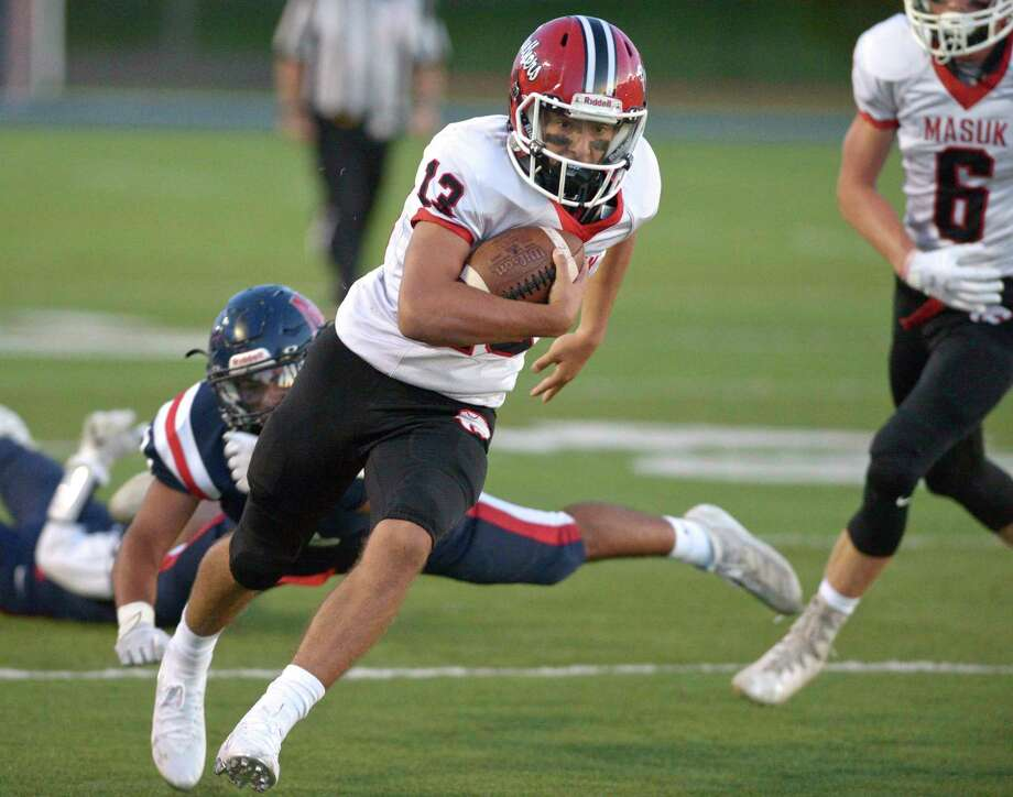 Masuk's Nicholas Saccu (13) beaks a tackle by New Fairfield's Nicholas Dimyan (3) to score a touchdown in the football game between Masuk and New Fairfield high schools, Friday night, September 13, 2019 at New Fairfield High School Rebel Field, New Fairfield, Conn. Photo: H John Voorhees III / Hearst Connecticut Media / The News-Times
