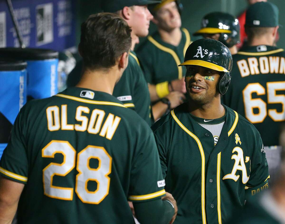 ARLINGTON, TEXAS - SEPTEMBER 13: Matt Olson #28 talks with Khris Davis #2 of the Oakland Athletics in the dugout after Davis' three-run home run in the third inning against the Texas Rangers at Globe Life Park in Arlington on September 13, 2019 in Arlington, Texas. (Photo by Richard Rodriguez/Getty Images)