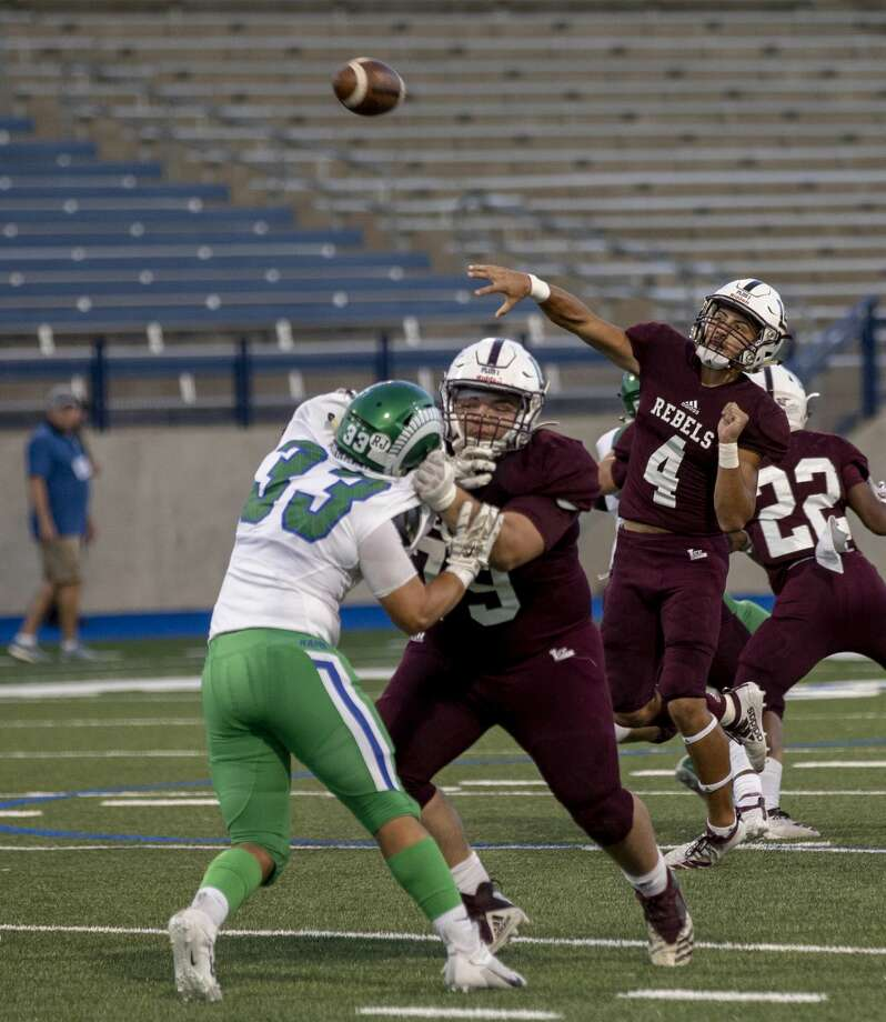 Lee's Mikey Serrano (4) throws the ball down the while field Lee's Ryan Pierce blocks El Paso Montwood's Julian Ramos (33) on Friday, Sept. 13, 2019 at Grande Communications Stadium. Photo: Jacy Lewis/Reporter-Telegram