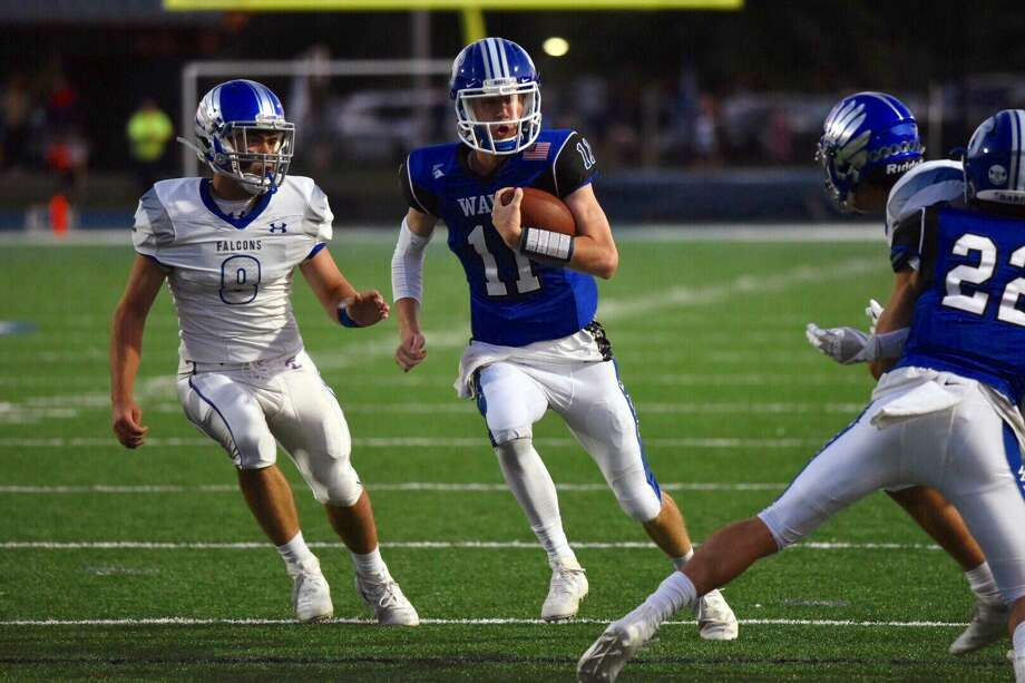 Darien QB Peter Graham runs for a first down with Ludlowe's James Bourque (8) in pursuit on Sept. 13, 2019. Photo: David Stewart / Hearst Connecticut Media / Connecticut Post