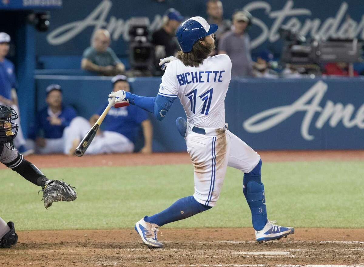Toronto Blue Jays designated hitter Bo Bichette (11) follows through as he hits a walkoff home run to defeat the New York Yankees in the 12th inning of a baseball game in Toronto, Friday, Sept. 13, 2019. (Fred Thornhill/The Canadian Press via AP)