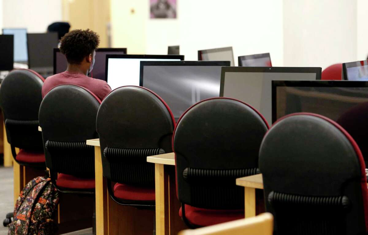 In this June 20, 2019, photo a Virginia Commonwealth University student works at a library workstation at the school in Richmond, Va. Students and their families can begin to submit two key applications for financial aid on Oct. 1 to help pay for higher education for the following school year. And filing early has its perks: better access to limited funds and a quicker response from schools on aid packages. (AP Photo/Steve Helber)