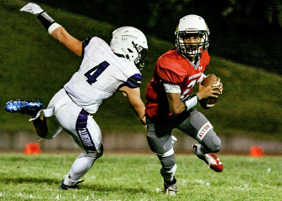 Alton Redbirds quarterback Andrew Jones scrambles from the pocket, eluding Collinsville pass rusher Jake Holten Friday night. Photo: Nathan Woodside | Hearst Illinois