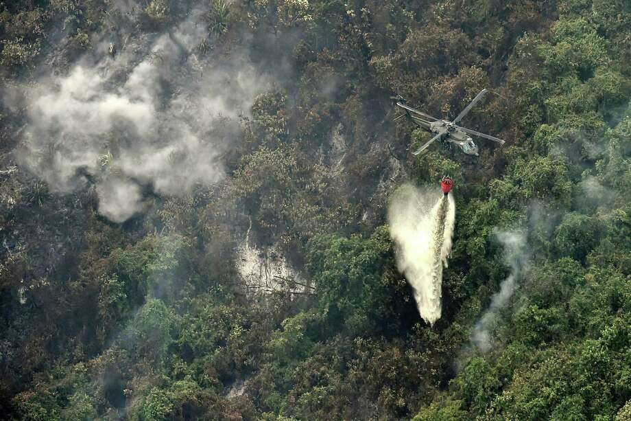 A Colombian Air Force helicopter helps fight a fire on Sept. 13 in Cali, Colombia, north of the Amazon basin. Photo: Luis Robayo / AFP /Getty Images / AFP or licensors