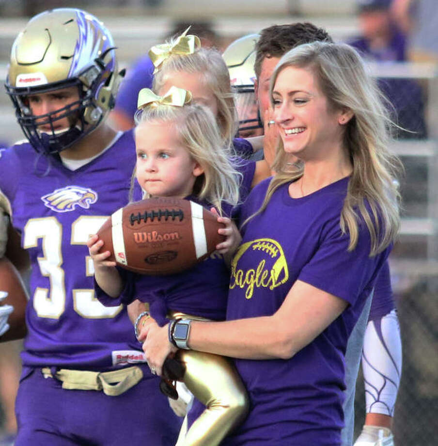 Three-year-old Sloane Toppmeyer delivers the game ball to officials while in the arms of her mother Sarah as the honorary captain for the Eagles in Civic Memorial's game vs. Cahokia Friday night at Hauser Field in Bethalto. Sloane and her family joined captains and coaches at midfield after her miraculous full recovery from an August swimming pool accident on her third birthday left her on life support systems with lung injuries during a 17-day stay at Cardinal Glennon Children's Hospital in St. Louis. Sloane's dad Adam Toppmeyer, behind Sloane and Sarah carrying oldest daughter Piper, was a CM football star before graduating in 2002. Photo: Greg Shashack / The Telegraph