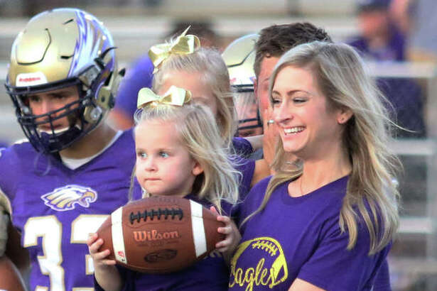 Three-year-old Sloane Toppmeyer delivers the game ball to officials while in the arms of her mother Sarah as the honorary captain for the Eagles in Civic Memorial's game vs. Cahokia Friday night at Hauser Field in Bethalto. Sloane and her family joined captains and coaches at midfield after her miraculous full recovery from an August swimming pool accident on her third birthday left her on life support systems with lung injuries during a 17-day stay at Cardinal Glennon Children's Hospital in St. Louis. Sloane's dad Adam Toppmeyer, behind Sloane and Sarah carrying oldest daughter Piper, was a CM football star before graduating in 2002.