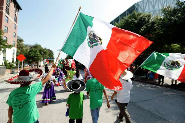 A man carries a large Mexican flag during the Houston Fiestas Patrias Parade downtown, celebrating the Mexican Independence Day, Saturday, Sept. 14, 2019, in Houston.