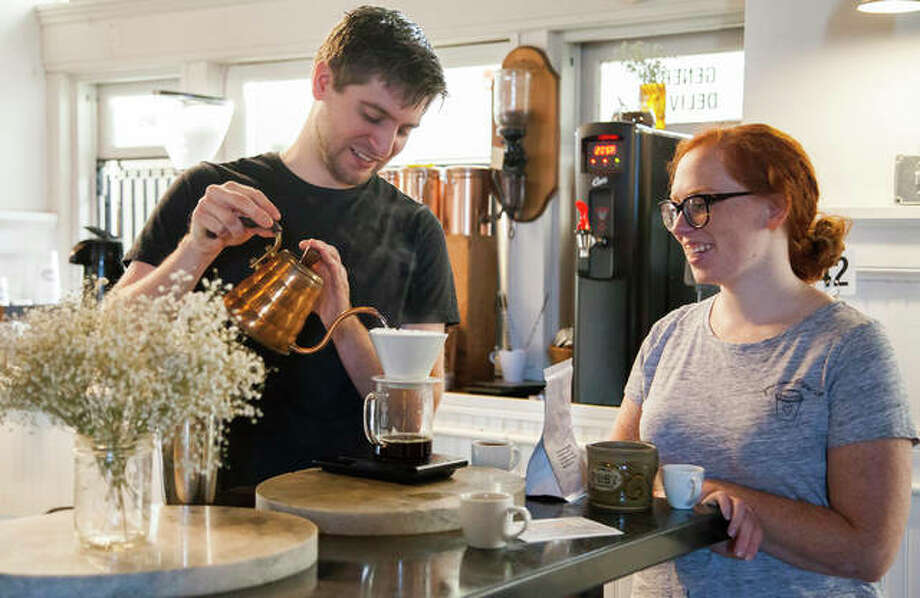 David McCann, left, shows Lydia Jackson the ropes at Post Commons on Alby Street in Alton. While taking different routes, three popular Alton coffee shops — Post Commons, Germania Brew Haus and Maeva's — are building a fanbase with great coffee. Photo: Jeanie Stephens|The Telegraph