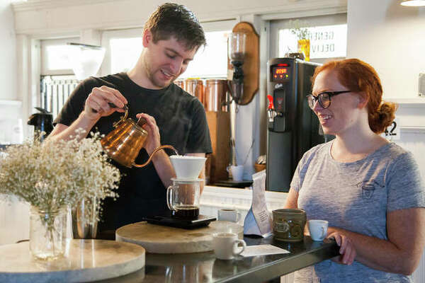 David McCann, left, shows Lydia Jackson the ropes at Post Commons on Alby Street in Alton. While taking different routes, three popular Alton coffee shops - Post Commons, Germania Brew Haus and Maeva's - are building a fanbase with great coffee.