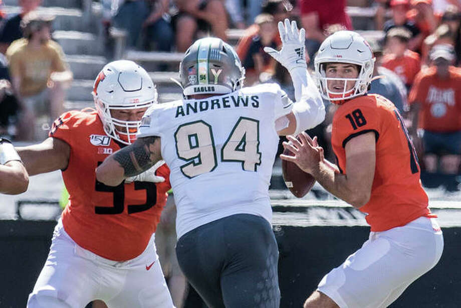 Illinois QB Brandon Peters (18) looks for a receiver as Eastern Michigan's Hunter Andrews (94) applies the pressure Saturday in Champaign. Photo: Associated Press
