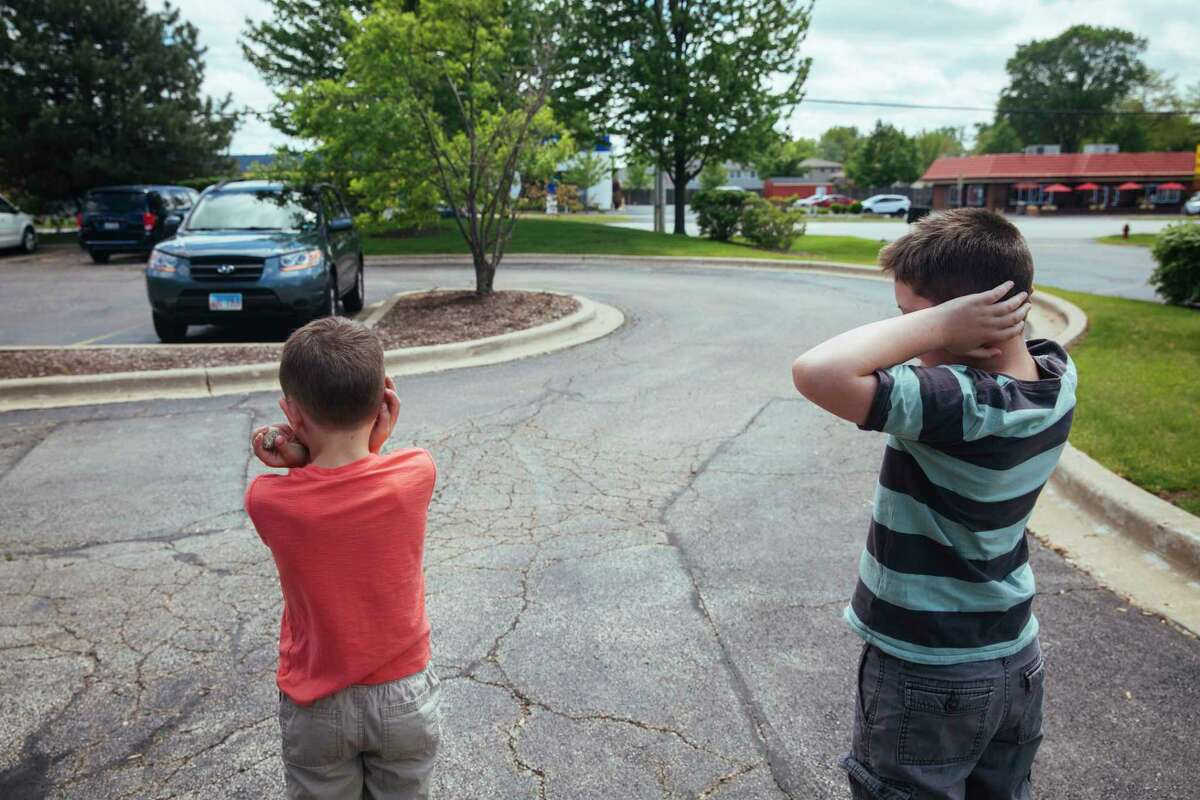 Danielle Rizzo's sons cover their ears as a loud vehicle drives by. Noise sensitivity is a common challenge for people with autism spectrum disorders.