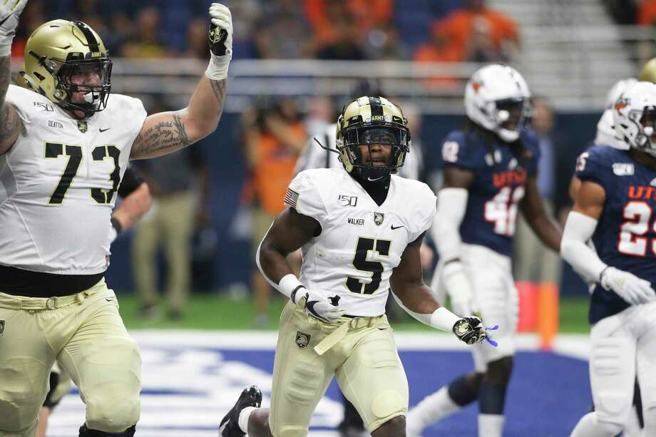 Army players Jaxson Deaton, 73, celebrates with running back Kell Walker after the their first touchdown as UTSA hosts Army at the Alamodome on Sept. 14, 2019. Photo: Tom Reel, Staff / Staff Photographer / 2019 SAN ANTONIO EXPRESS-NEWS
