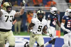Army players Jaxson Deaton, 73, celebrates with running back Kell Walker after the their first touchdown as UTSA hosts Army at the Alamodome on Sept. 14, 2019.