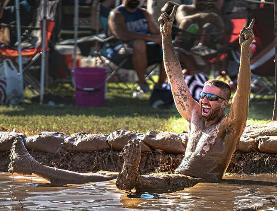 A mud volleyball player celebrates Saturday afternoon during one of a day full of matches at Liberty Bank Alton Amphitheater for another year of the rejuvenated Alton Expo. Photo: Nathan Woodside | The Telegraph