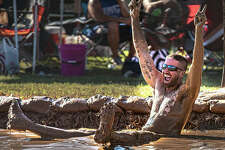A mud volleyball player celebrates Saturday afternoon during one of a day full of matches at Liberty Bank Alton Amphitheater for another year of the rejuvenated Alton Expo.