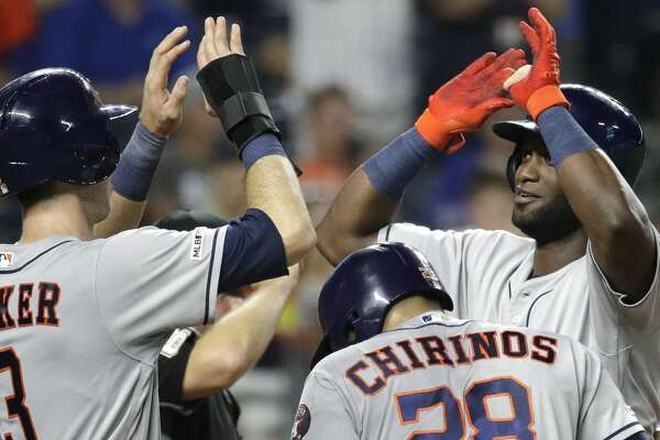 Houston Astros' Yordan Alvarez, right, celebrates with Kyle Tucker (3) and Robinson Chirinos (28) after hitting a three-run home run during the eighth inning of the team's baseball game against the Kansas City Royals on Saturday, Sept. 14, 2019, in Kansas City, Mo. (AP Photo/Charlie Riedel)