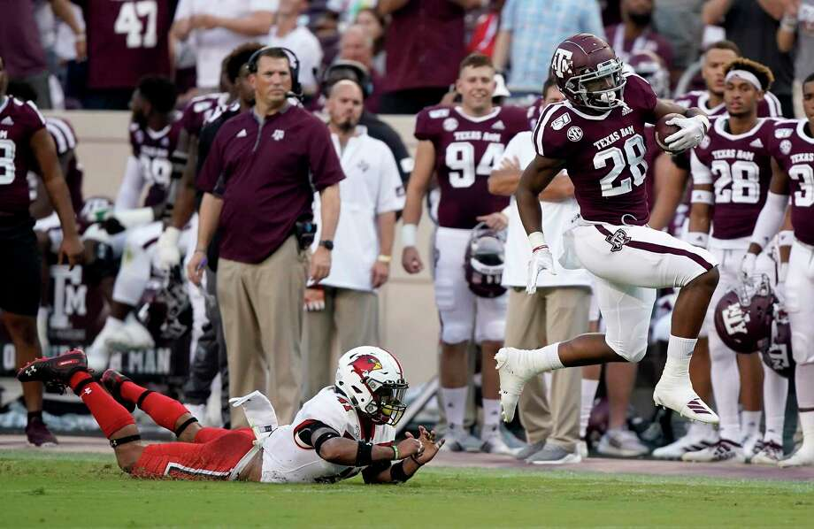 Texas A&M running back Isaiah Spiller (28) is tripped up by Lamar defensive back Michael Lawson (41) after a first down run during the first half of an NCAA college football game, Saturday, Sept. 14, 2019, in College Station, Texas. (AP Photo/Sam Craft) Photo: Sam Craft, FRE / Associated Press / Copyright 2019 The Associated Press. All rights reserved.