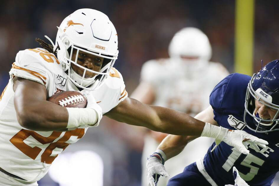 Texas Longhorns running back Keaontay Ingram (26) dodges a hit by Rice Owls cornerback Andrew Bird (15) to run the ball in for a touchdown in the second quarter against Rice University at NRG Stadium in Houston on Saturday, Sept. 14, 2019.