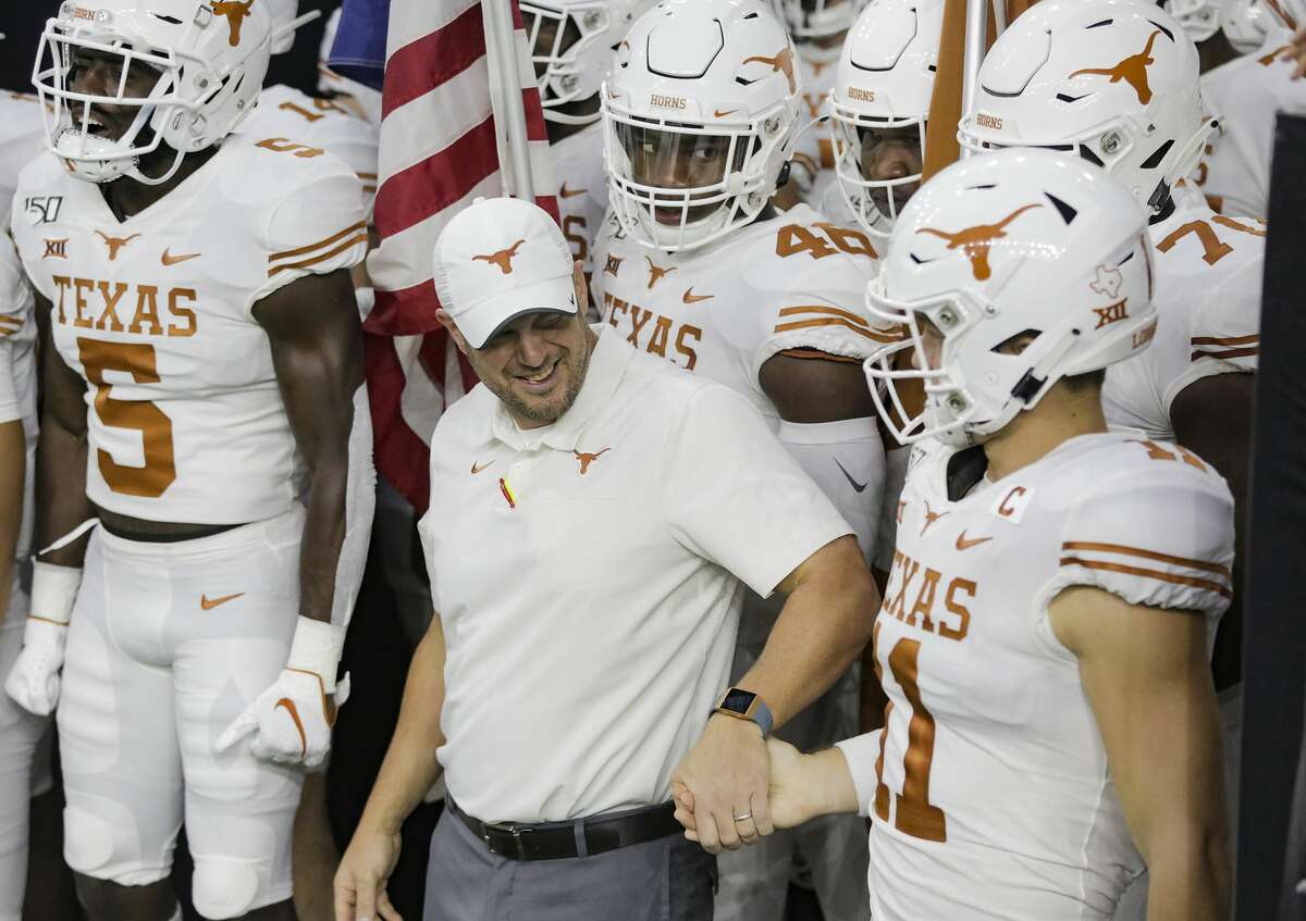 Texas Longhorns head coach Tom Herman shakes hands with Texas Longhorns quarterback Sam Ehlinger (11) before the team takes to the field at NRG Stadium in Houston on Saturday, Sept. 14, 2019.