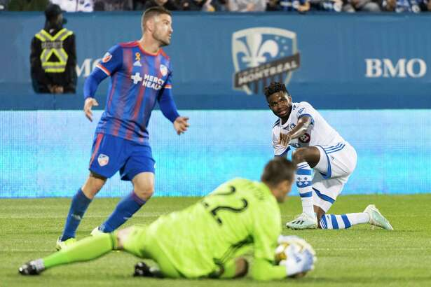 Montreal Impact's Orji Okwonkwo, right, watches after taking a shot on FC Cincinnati goaltender Przemyslaw Tyton (22), as Cincinnati's Greg Garza defends during the first half of an MLS soccer match Saturday, Sept. 14, 2019, in Montreal. (Graham Hughes/The Canadian Press via AP)