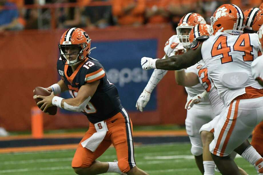 Syracuse quarterback Tommy Devito, left, scrambles away from the Clemson defense during the first half of an NCAA college football game Saturday, Sept. 14, 2019, in Syracuse, N.Y. (AP Photo/Steve Jacobs) Photo: Steve Jacobs / Copyright 2019 The Associated Press. All rights reserved.