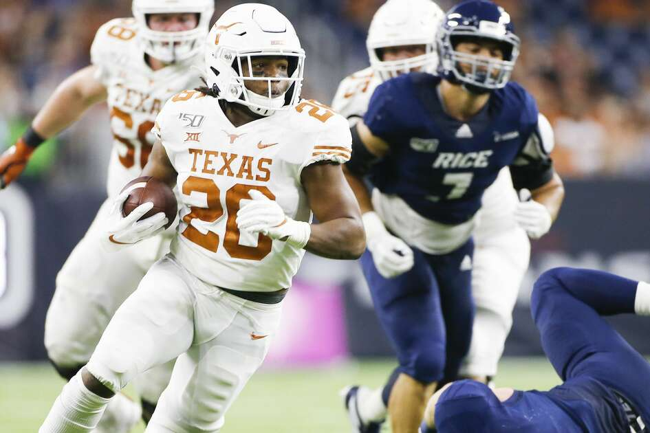 Texas Longhorns running back Keaontay Ingram (26) dodges a hit to run the ball in for a touchdown in the second quarter against Rice University at NRG Stadium in Houston on Saturday, Sept. 14, 2019.