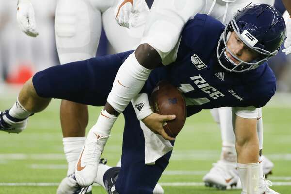 Rice Owls quarterback Tom Stewart (14) gets out from under Texas Longhorns linebacker Jeffrey McCulloch (23) after sliding for a first down at NRG Stadium in Houston on Saturday, Sept. 14, 2019.