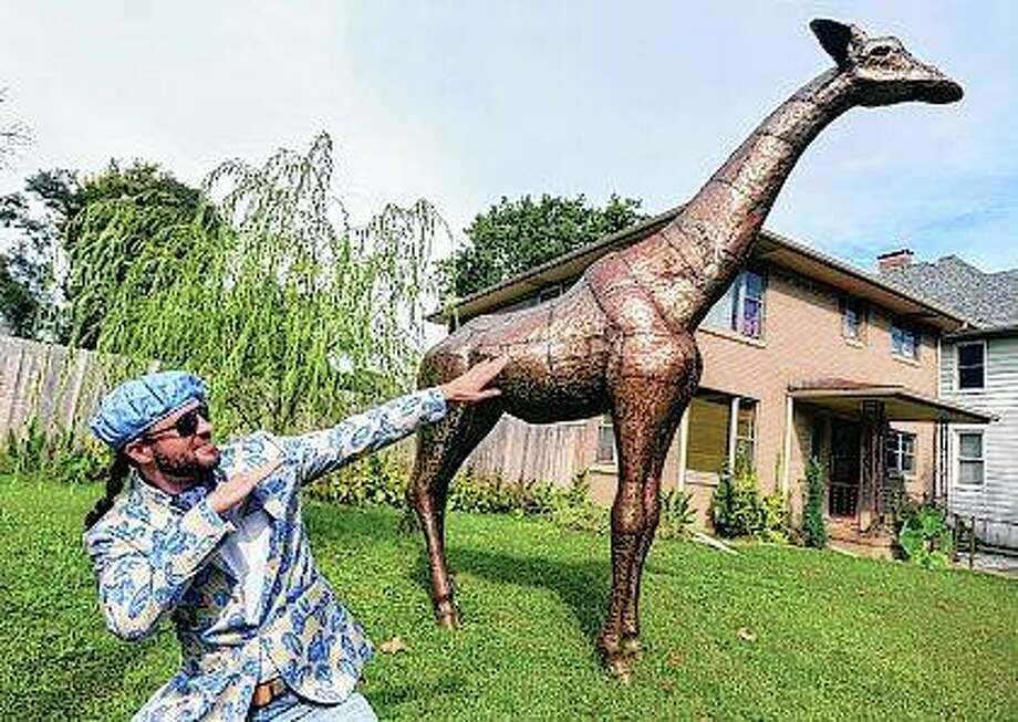 Artist Monte de Gallo shows off his life-size 14-foot steel sculpture of a giraffe on display at a house in Peoria. The affable sculptor has turned his talent into a business creating and selling the creatures, which are crafted from salvaged steel. Photo: Matt Dayhoff | Journal Star (AP)